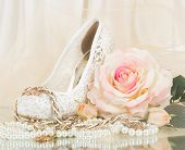 stock photo of wench  - The beautiful bridal rose with wedding shoe and beads - JPG