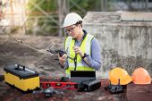 Asian Engineer Man Working With Drone, Laptop And Working Tools At Construction Site. Male Worker Us poster