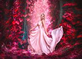 Beauty romantic young woman in long chiffon dress with gown posing in the fantasy forest in red lush poster
