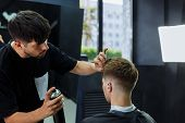 Barber Makes Hair Styling With Hair Spray After Haircut At The Barber Shop. Young Handsome Caucasian poster