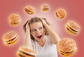 Diet Concept. Young Woman Is Under Stress, Burgers Are Flying Around