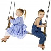 A preschool brother and sister swinging on an antique, 2-person, wooden pump-style swing.  The girl