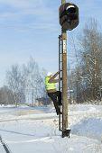 Trabajador ferroviario escalada en poste de balizas de señal