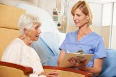 stock photo of geriatric  - Nurse Taking Notes From Senior Female Patient Seated In Chair By Hospital Bed - JPG