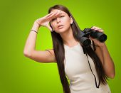 Portrait Of A Young Woman Holding Binoculars And Searching against a green background