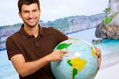 Young Man Showing Destination On Globe, Outdoors poster