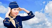 Beautiful  smiling stewardess in uniform on a background sky