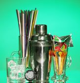 Cocktail shaker and  other bartender equipment on color background