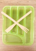 Green plastic cutlery tray with crossed wooden fork and scapula on wooden table