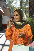 picture of dupatta  - Happy Indian woman using cell phone while holding shopping bags - JPG
