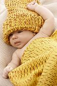 Lovely newborn baby in yellow knitwear.