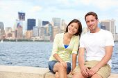 Young couple dating in New York. Portrait of multi-ethnic couple with Manhattan and New York City Skyline in background. Asian woman, Caucasian man tourists on Ellis Island, New York City, USA