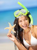 Summer beach vacation holidays woman wearing snorkeling mask showing star happy joyful and laughing. Summer travel getaway concept with multiracial Asian Chinese / Caucasian woman in bikini in the sun