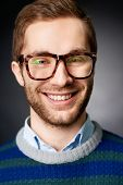 Portrait of attractive male in eyeglasses looking at camera with smile