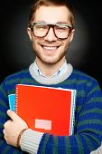 Portrait of happy student in eyeglasses holding copybooks and looking at camera with smile