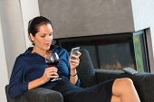Woman businesswoman texting sms mobile phone living room drinking wine