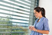 Young woman day dreaming looking window blinds drinking tea