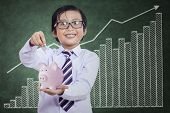 stock photo of japanese coin  - Little boy puts the coin into the piggy bank at classroom - JPG