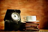 Old clock, coffee and vintage books on grunge background
