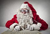 nerd Santa Claus writes with keyboard
