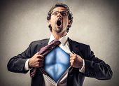 stock photo of superman  - businessman unbuttons his suit and becomes superman - JPG