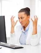 business, office, school and education concept - stressed african businesswoman with computer at wor