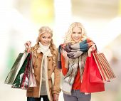 retail and sale concept - happy women in winter clothes with shopping bags