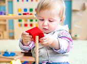 cute little girl in the classroom early development plays with bright toys