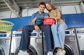 Portrait of couple with clothes basket sitting on top of washing machine in laundry