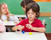 stock photo of molding clay  - Little boy molding clay with female friend in background at classroom - JPG