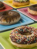 Selection Of Ring Doughnuts On A Different Coloured Plates