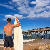 Boy surfer back rear view holding surfboard on Newport pier beach California [photo-illustration]