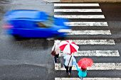 stock photo of street-walker  - a pedestrian crossing with blue car in rain - JPG