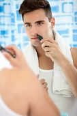 Young man remove hair from his nose with trimmer