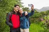 stock photo of selfie  - Happy couple on a hike taking a selfie in the countryside - JPG