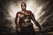 foto of legion  - Wounded gladiator  with sword against stormy sky - JPG