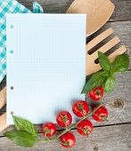 Blank notepad paper for your recipes with tomatoes and basil on wooden table