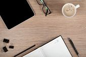 Tablet, notepad, glasses and coffee cup on office wooden table