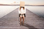 woman sitting on a wharf with a box in her face