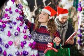 Happy young woman shopping for Christmas decorations with man in store