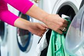 stock photo of dirty-laundry  - Young woman in a launderette - JPG