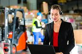 Friendly Woman, dispatcher or supervisor using headset and laptop at warehouse of forwarding company