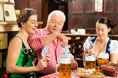 In Pub - friends in Tracht, Dirndl and Lederhosen drinking a fresh beer in Bavaria, Germany playing cards