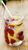 A jar full of cold drink with lemon and raspberries over a wooden surface