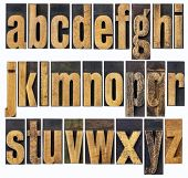 complete English lowercase alphabet - a collage of 26 isolated antique wood letterpress printing blocks, scratched and stained by inks