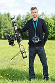 Portrait of confident technician standing with UAV helicopter and remote control in park