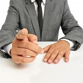 man wearing a suit sitting in a table pointing the finger to the observer