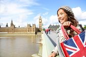 London woman holding shopping bag near Big Ben. Happy woman shopper smiling during travel vacation in London. Multicultural Asian Caucasian female traveler on Westminster Bridge.