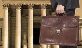 stock photo of magistrate  - A lawyer with a briefcase on the background of the courthouse - JPG
