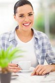 beautiful woman drinking coffee at home while calculating her financial